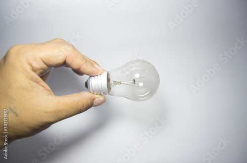 Hand of holding illuminated light bulb, innovation inspiration concept ,business Wallpaper Mural