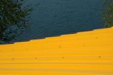 Bright-yellow Corrugated Iron Roof Of A Hut Near The Lake