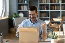Excited Happy Man Looking Into Cardboard Box, Sitting At Work Desk, Received Parcel With Awaited Online Store Order, Smiling Laughing Young Male Celebrating Success, Lottery Winner Prize
