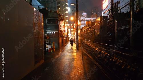 Fotografía Illuminated Footpath Amidst Buildings At Night