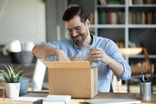 Smiling man wearing glasses unpacking awaited parcel, looking inside, sitting at Fototapete