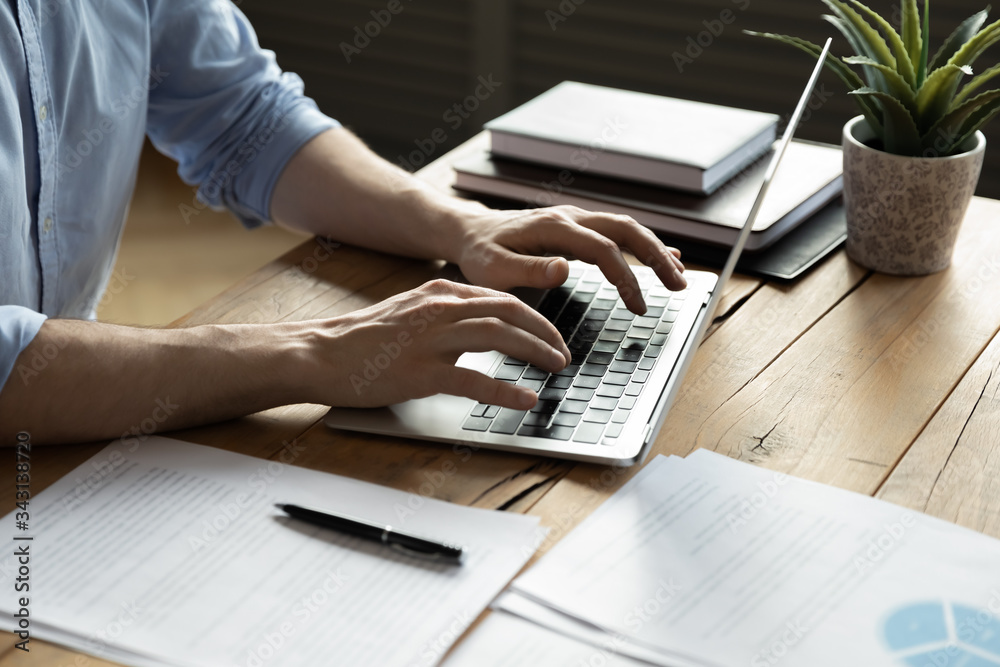 Fototapeta Close up businessman using laptop, typing on keyboard, sitting at wooden desk with documents, writing email, accountant writing financial report, busy student studying online, searching information