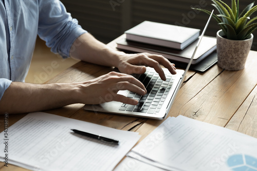 Cuadros en Lienzo Close up businessman using laptop, typing on keyboard, sitting at wooden desk wi