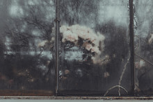 A Blurry Foggy Window With Dripping Rain Drops On The Cracked Glass. Background With Condensate Flowing Water On The Window Glass..High Air Strong Humidity, Drops. Trees Reflection. Colorful Flowers