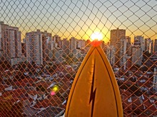 Surfboard By Chainlink Fence Against Sky During Sunset In City