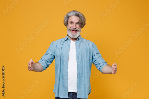 Photographie Excited elderly gray-haired mustache bearded man in blue shirt isolated on yellow wall background