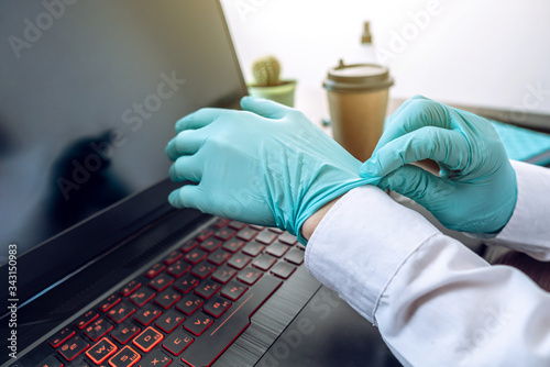 Photo Woman putting on a pair of rubber mint gloves before working at a computer