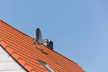 Satellite Dish On A Red Roof T...