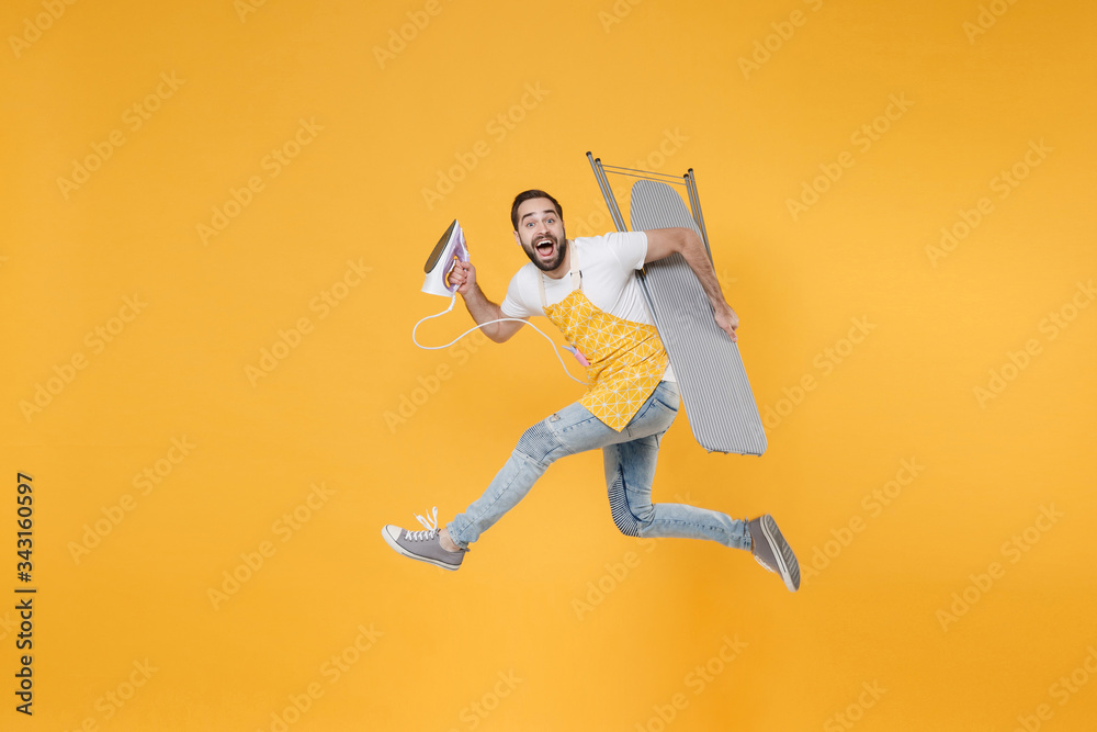 Fototapeta Side view of excited young man househusband in apron rubber gloves hold iron board for ironing while doing housework isolated on yellow background studio. Housekeeping concept. Jumping looking camera.