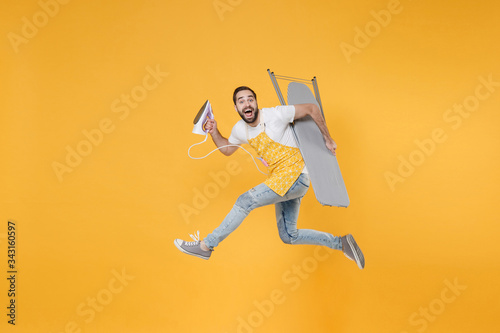 Photo Side view of excited young man househusband in apron rubber gloves hold iron board for ironing while doing housework isolated on yellow background studio