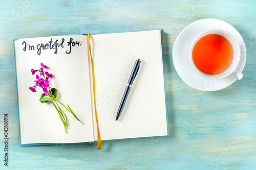 Gratitude journal with a pen and a cup of tea, with the handwritten phrase I am Canvas Print