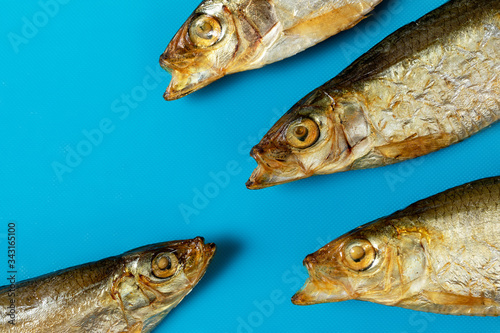 Photo Three smoked fish with their mouths open in front of one fish on a blue background