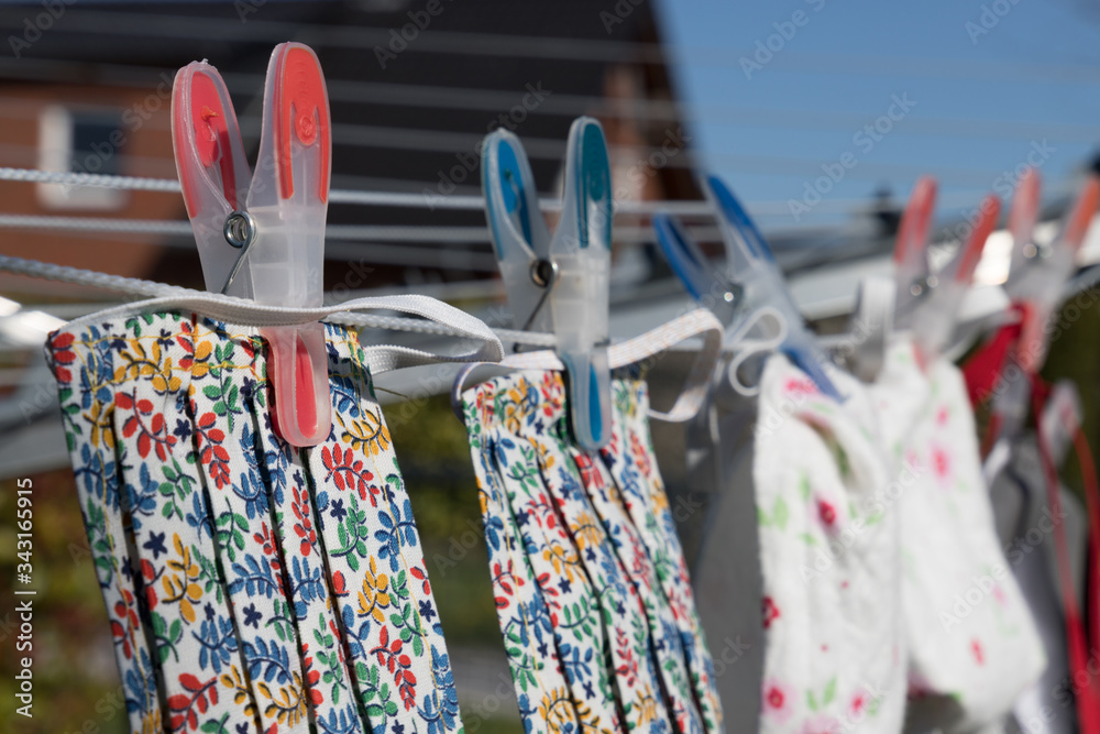 Fototapeta handmade face mask on clothes line to wear in corona crisis