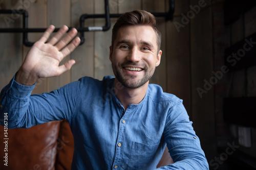 Headshot portrait of happy Caucasian young man sit in cafe wave greeting talking Tapéta, Fotótapéta