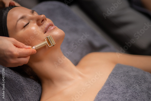 professional masseur use derma roller for lifting face care, clients came in lux Fototapet