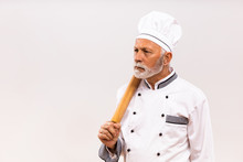 Image Of Angry Senior Chef Holding Rolling Pin On Gray Background.