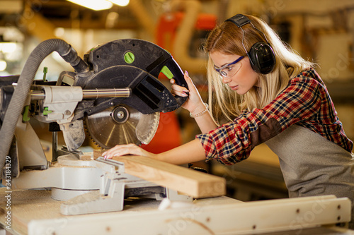 Obraz concentrated woman carpenter behind powerful electric machine, woman use circular sawer for wood cutting - fototapety do salonu