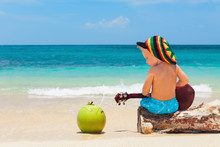 Little Baby In Rasta Hat Play Reggae Music On Hawaiian Ukulele, Enjoy Relaxing On Ocean Beach. Kids Healthy Lifestyle. Family Summer Holiday. Activity On Tropical Jamaica And Caribbean Island Travel.