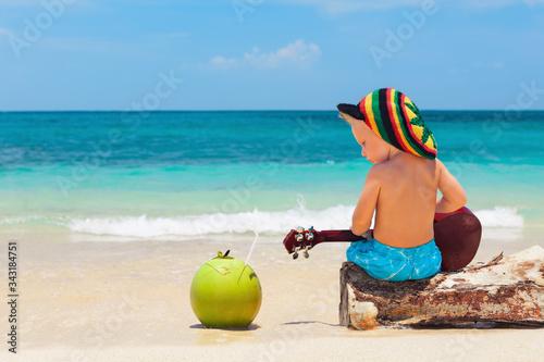 Fotografie, Obraz Little baby in rasta hat play reggae music on Hawaiian ukulele, enjoy relaxing on ocean beach