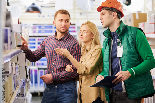 helpful affable warehouse worker help customers with choice, man use document wh Canvas Print