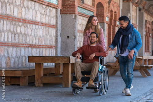Photo Paralyzed young man in a wheelchair accompanied by a young man and a girl stroll