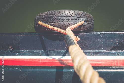 Looking down at a rubber tire on the side of a boat, used as a marine fender bum Wallpaper Mural
