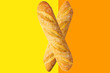 canvas print picture - Freshly baked artisan whole french baguettes with golden crusty floury texture on duotone yellow orange background. Poster banner for bakery restaurant cafe. Bread making concept