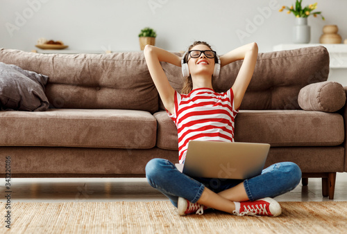 Fototapeta Pleased young woman in headphones with laptop listening to music while relaxing on sofa at home obraz
