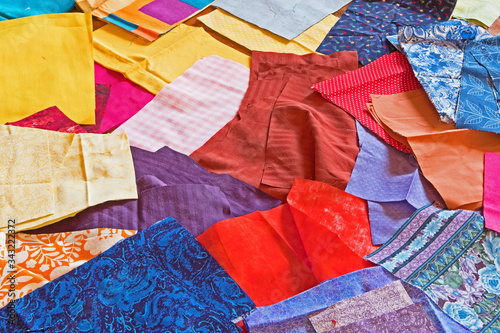 Canvastavla A patchwork of brightly colored cloth material is waiting to be sewn into homemade face masks