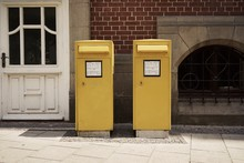 Yellow Mailboxes Against Building
