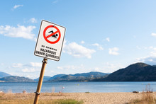 No Swimming Sign Warning Of Hazardous Under Currents With View Of Beach, Lake, And Blue Sky