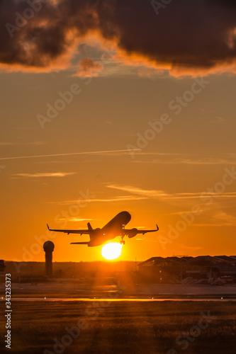 Start samolotu o zachodzie słońca z Gdańskiego Lotniska imienia Lecha Wałęsy  Fotobehang