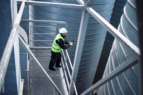 Factory silos worker standing on metal platform between industrial storage tanks and looking at tablet about food production Canvas-taulu