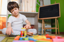 Little Sad Thoughtful Bored Toddler Boy Playing Colorful Building Blocks Alone At Home During Quarantine. Development Game. Loneliness At Self Isolation Period