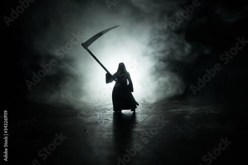 Fotografía Death with a scythe in the dark misty forest