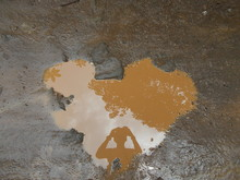 Reflection Of Person On Heart Shaped Puddle At Dirt Road