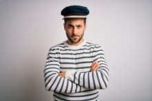 Young Handsome Sailor Man With Beard Wearing Navy Striped Uniform And Captain Hat Skeptic And Nervous, Disapproving Expression On Face With Crossed Arms. Negative Person.