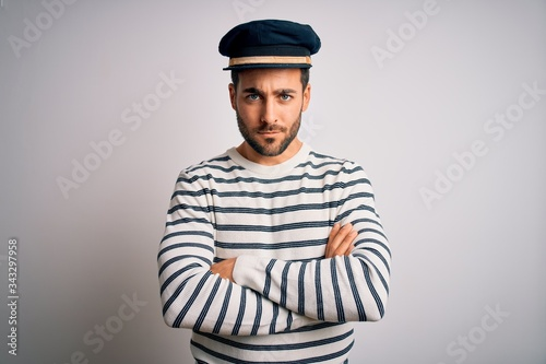 Fototapeta Young handsome sailor man with beard wearing navy striped uniform and captain hat skeptic and nervous, disapproving expression on face with crossed arms