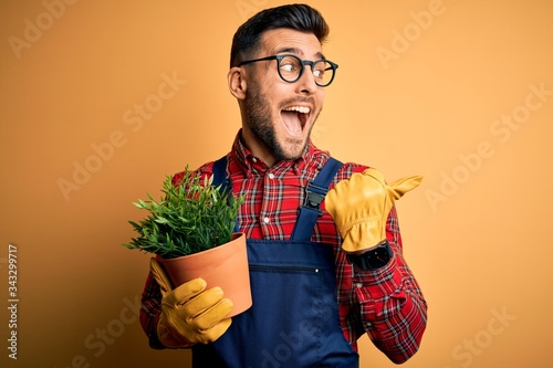 Canvas-taulu Young gardener man wearing working apron gardening plat for hobby over yellow ba