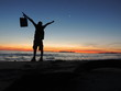 Full Length Of Silhouette Man With Arms Outstretched At Beach Against Sky During Sunset