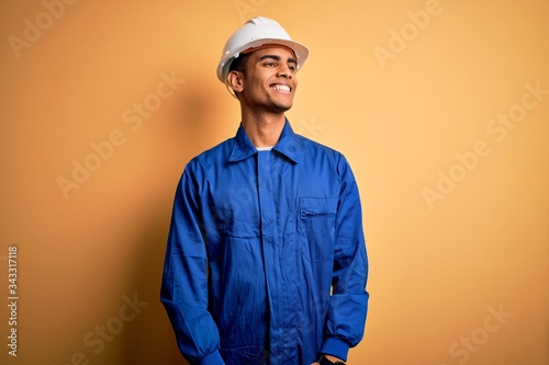 Obraz na plátně Young handsome african american worker man wearing blue uniform and security helmet looking away to side with smile on face, natural expression