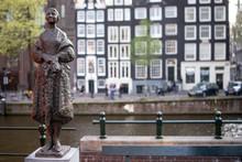 Piccola Statua Scultura In Bronzo Di Donna In Piedi Vestita E Avvolta Nel Suo Scialle Posta Lungo Un Canale In Città