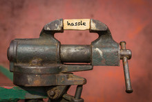 Vice Grip Tool Squeezing A Plank With The Word Hassle