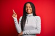 canvas print picture - Young african american woman wearing turtleneck sweater over red isolated background with a big smile on face, pointing with hand and finger to the side looking at the camera.