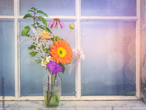 Decorative mixed floral bouquet in glass bottle on marble ledge in front of old Canvas Print