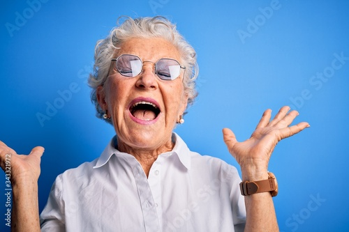 Senior beautiful woman wearing elegant shirt and glasses over isolated blue background celebrating mad and crazy for success with arms raised and closed eyes screaming excited Wallpaper Mural