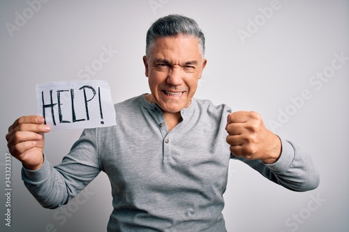 Middle age handsome grey-haired man holding paper with help message annoyed and Canvas Print