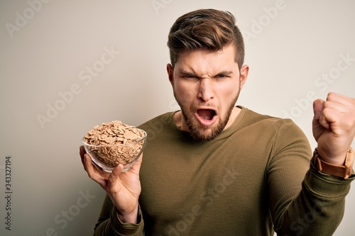 Young blond man with beard and blue eyes holding bowl with cornflakes cereals an Wallpaper Mural
