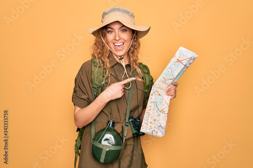 Tablou Canvas Young blonde explorer woman with blue eyes hiking wearing backpack holding city