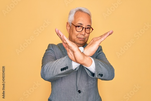 Fototapety, obrazy: Middle age senior grey-haired handsome business man wearing glasses over yellow background Rejection expression crossing arms doing negative sign, angry face